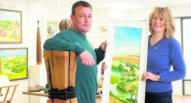 Witney Gazette: Gallery owner Andrew Harrison, sculptor of the wooden piece he is leaning on, and Carolyn Tyrer holding one of her works