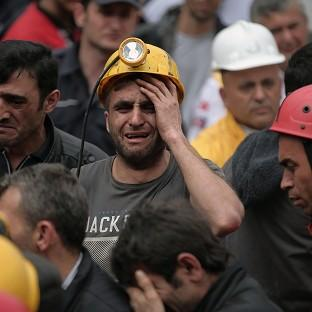A miner cries as rescue workers carry the dead body of a colleague from the mine in Soma