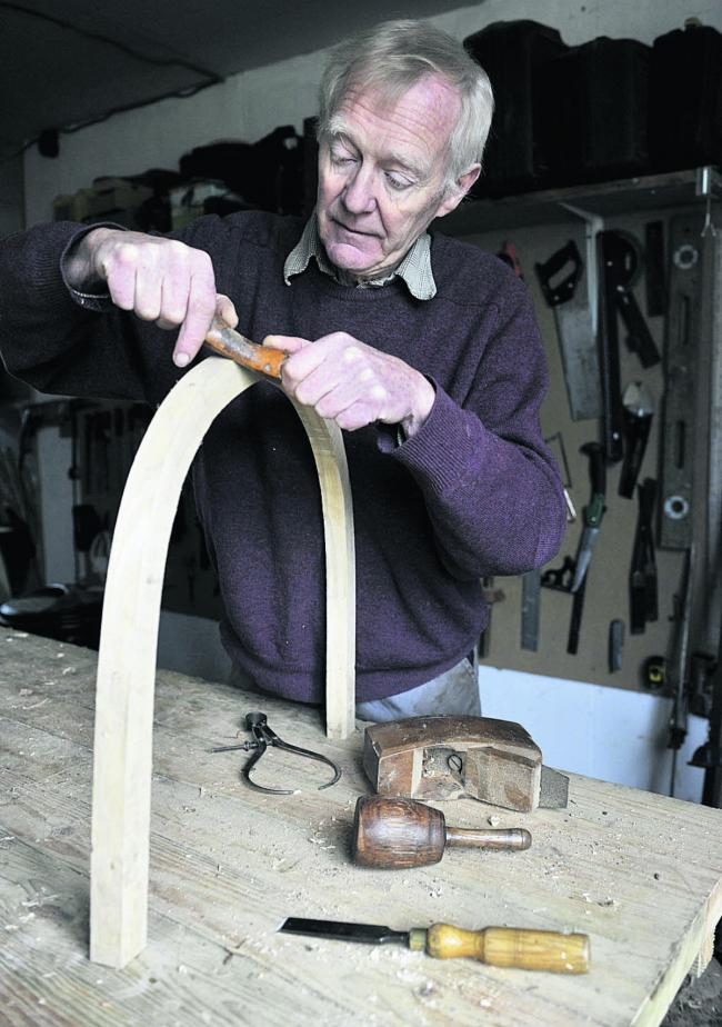 James Gray shapes a chair back in his workshop