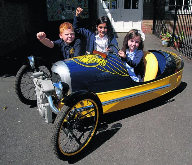 Witney Gazette: From left, Rex Chiles, seven, Maya Rees, 10, and Poppy Rooney, four, try the Morgan pedal car for size