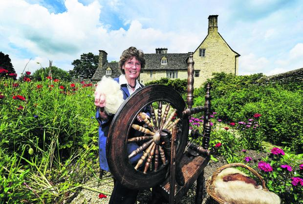 Witney Gazette: Sue Tucker spinning yarn on a wooden spinning wheel at Cogges Farm Museum in Witney