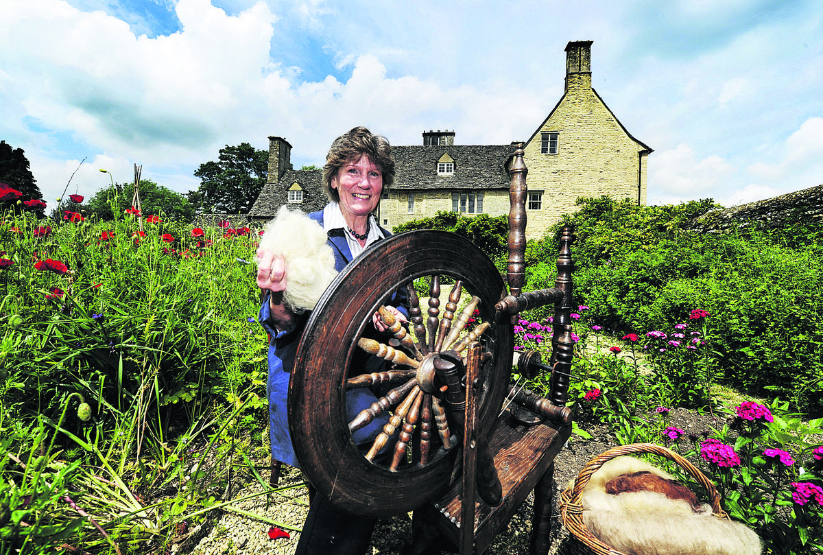 Sue Tucker spinning yarn on a wooden spinning wheel at Cogges Farm Museum in Witney