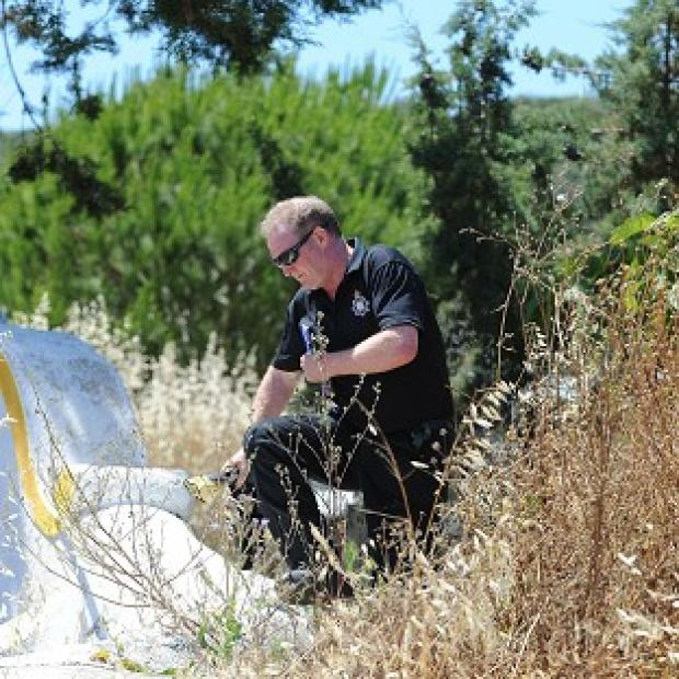 Witney Gazette: A British police officer scrambles over a wall as British and Portuguese officers investigate the disappearance of Madeleine McCann from Praia da Luz