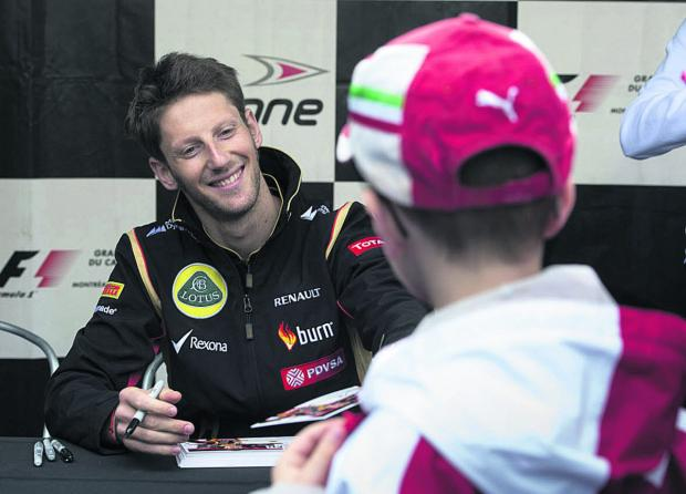 Lotus driver Romain Grosjean signs autographs for a young fan at the Canadian Grand Prix