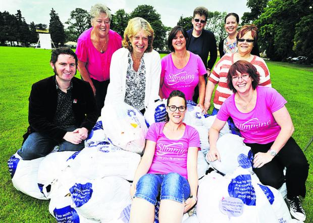 From left, Andrew Brooks, Brenda Moody-Chandler, Maggie Burton, Aileen Mitchell, Sandra Edwards, Sian Bennett, Jenny Walker and Adrienne Black, with Amber Wing, front, with the bags of clothes at The Leys in Witney