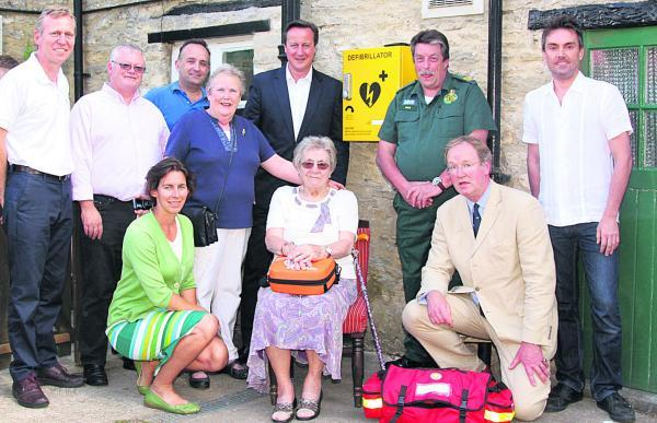 Witney Gazette: Prime Minister David Cameron and Dick Tracey, next to the defibillator box, with Hailer residents and GP Dr Robin Carr, front, right
