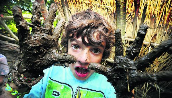 Witney Gazette: Luke Shirley, aged seven, gets his hands mucky daubing mud at the Hill End Centre. Picture: OX68288 Damian Halliwell