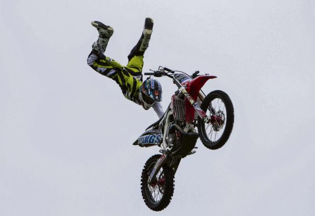 Witney Gazette: THE SHOW MUST GO ON: A stunt rider from the Bolddog Lings daredevil motorbike team soars across a grey sky at Great Aycliffe Show last year