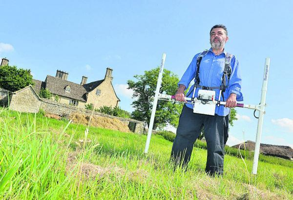 Archaeology student Daniel May uses a gradiometer at Cogges Manor Farm