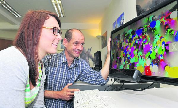 Mark Saville watches Marta Dabek using an Eyegaze tracking unit to paint on a computer screen at SpecialEffect's headquarters