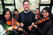 Director of music John Hutchings with violinists, from left, Tiffany Fing, 17, Agnes So, 16, Jenny To, 16, and Jenny Bae, 16.  Picture: OX71115 Jon Lewis