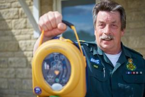 Dick Tracey handing over a a portable automatic external defibrillator (AED) to Bicester Eco-town. Picture: Cliff Hide