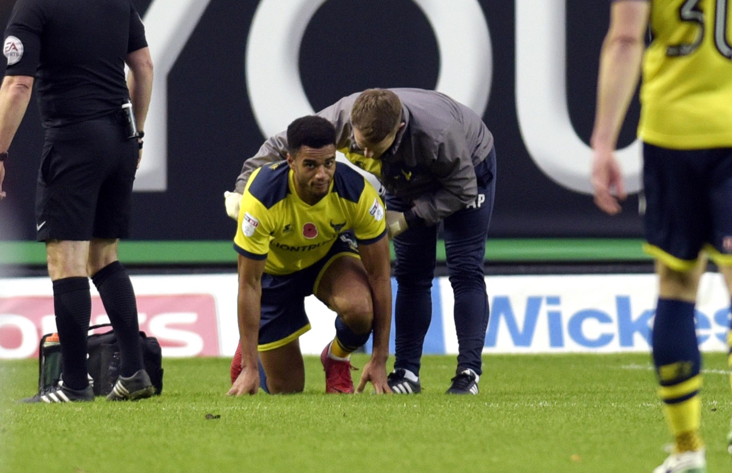 Oxford United captain Curtis Nelson receives treatment on Saturday. He was forced to leave the pitch on a stretcher Picture: David Fleming
