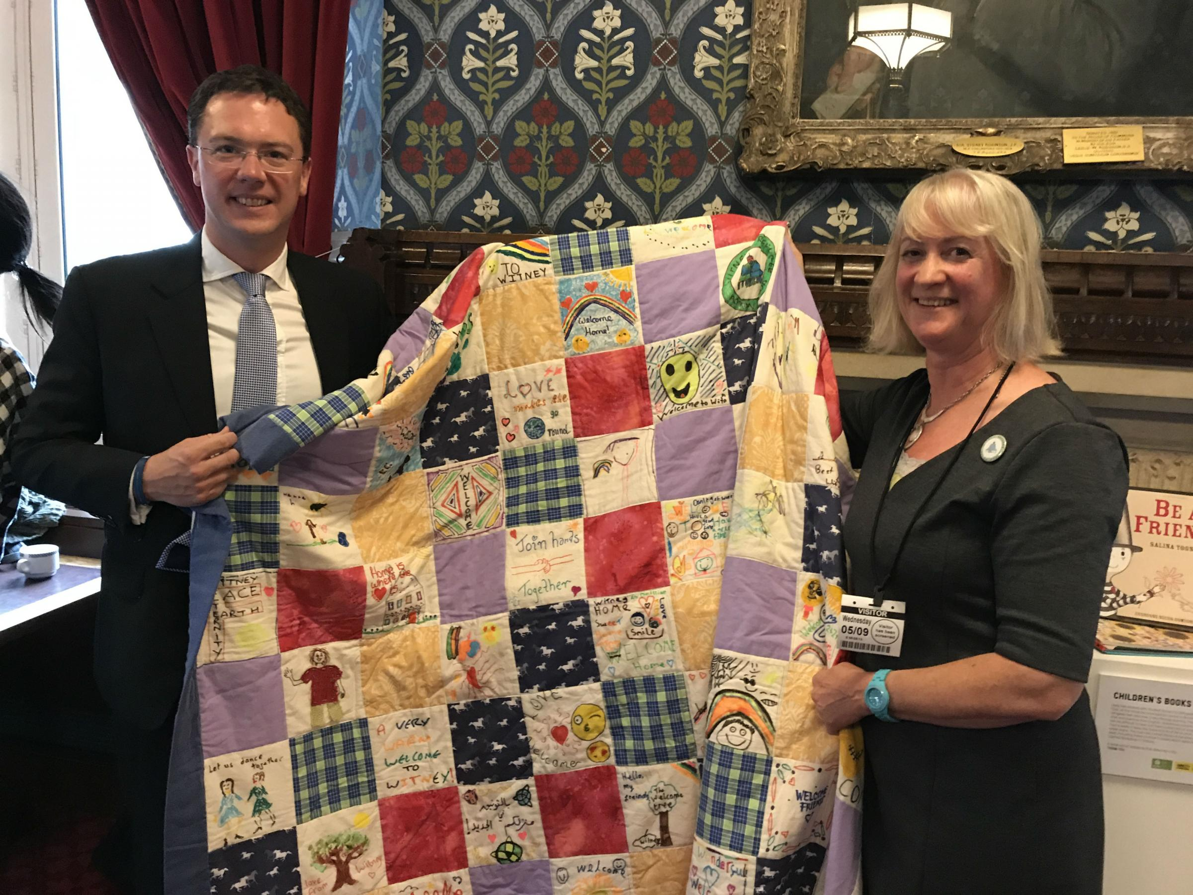PROUD: Witney MP Robert Courts and Liz Duncan from Witney Refugee Action Group hold the quilt in Parliament 		Picture: Kai Tabacek